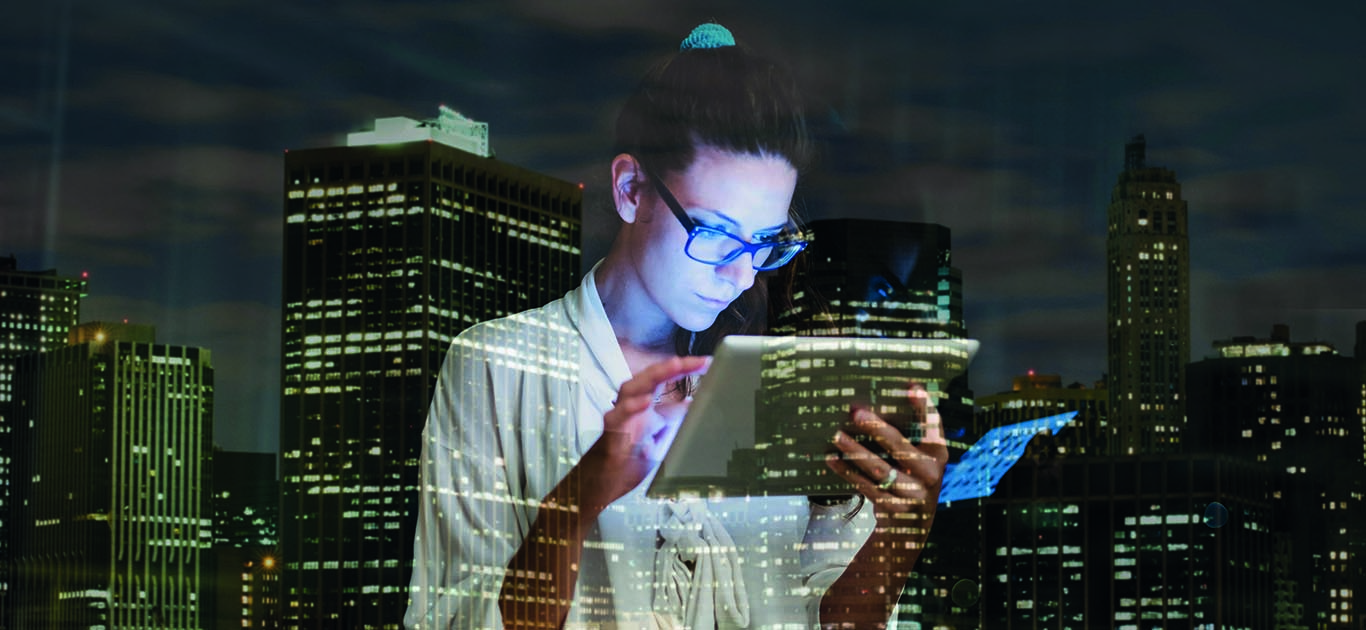 Young woman using digital tablet at home against city lights
