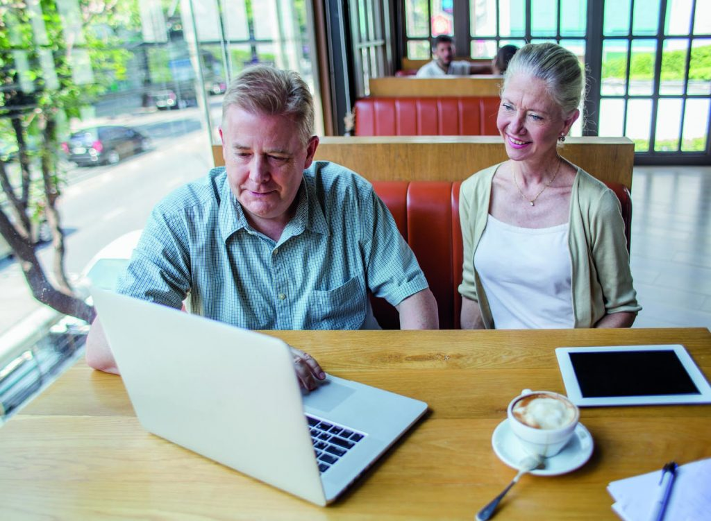 Man and a woman in a cafe with lap top
