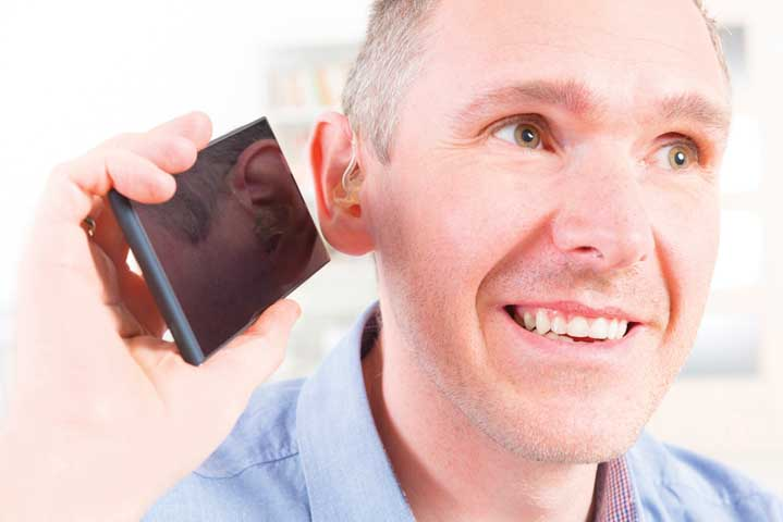 Hearing impaired man talking using mobile phone at home